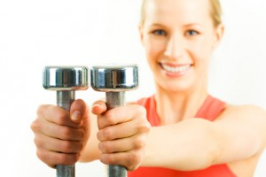 Horizontal image of metal dumbbells in woman's hands